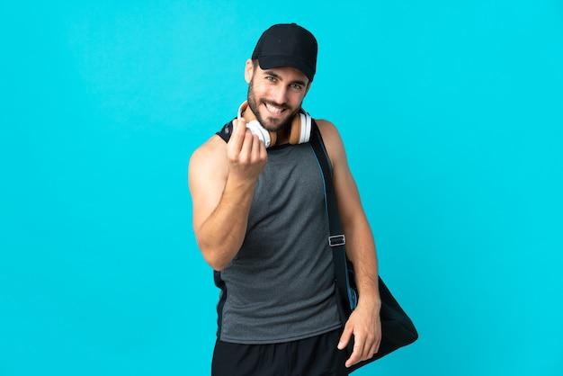 Молодой спортивный человек со спортивной сумкой, изолированной на синем, делая денежный жест
