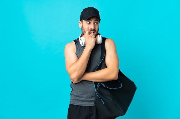 Молодой спортивный человек со спортивной сумкой, изолированной на синем, нервничает и испуган