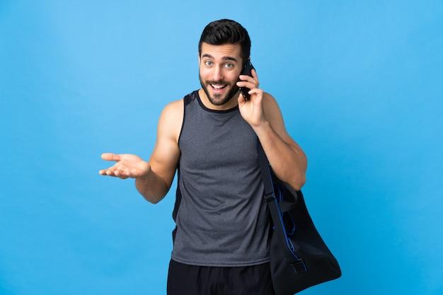 Молодой спортивный человек с спортивной сумкой на синей стене, ведущий разговор с кем-то по мобильному телефону