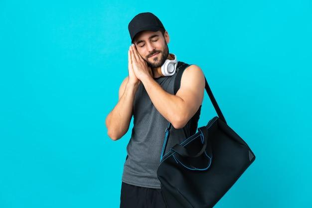 젊은 스포츠 가방 dorable 식 파란색 제스처를 만드는 파란색 벽에 고립 된 스포츠 가방