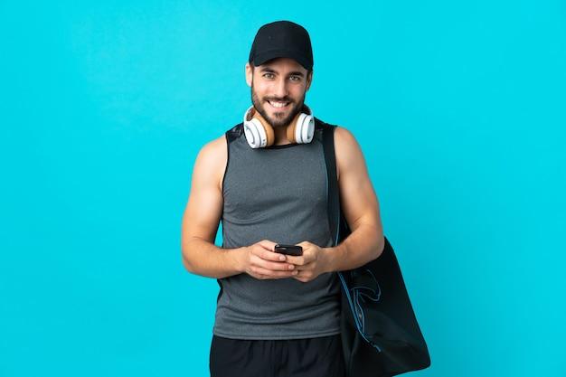 모바일로 메시지를 보내는 파란색 벽에 고립 된 스포츠 가방 젊은 스포츠 남자