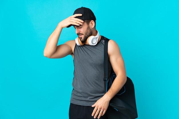 頭痛と青い壁に分離されたスポーツバッグを持つ若いスポーツ男