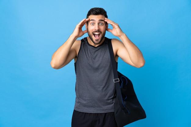 驚きの表情で青に分離されたスポーツバッグを持つ若いスポーツ男