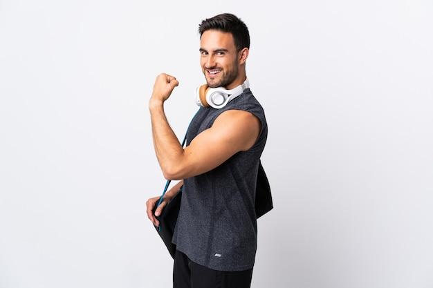 強いジェスチャーをしている白い背景で隔離のスポーツバッグを持つ若いスポーツ男