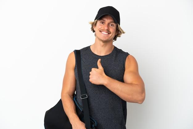 Молодой спортивный человек со спортивной сумкой, изолированной на белом фоне, показывая жест пальца вверх