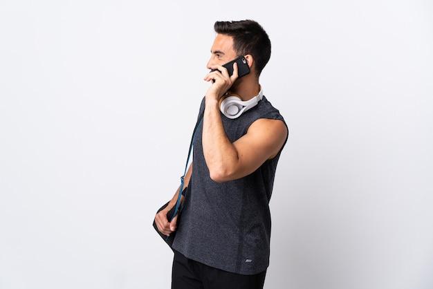 누군가와 휴대 전화로 대화를 유지하는 흰색 배경에 고립 된 스포츠 가방 젊은 스포츠 남자
