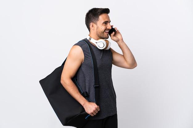 휴대 전화와 대화를 유지하는 흰색 배경에 고립 된 스포츠 가방 젊은 스포츠 남자