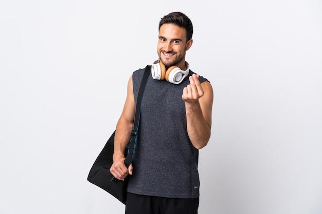 Молодой спортивный человек со спортивной сумкой, изолированные на белом фоне, делая денежный жест