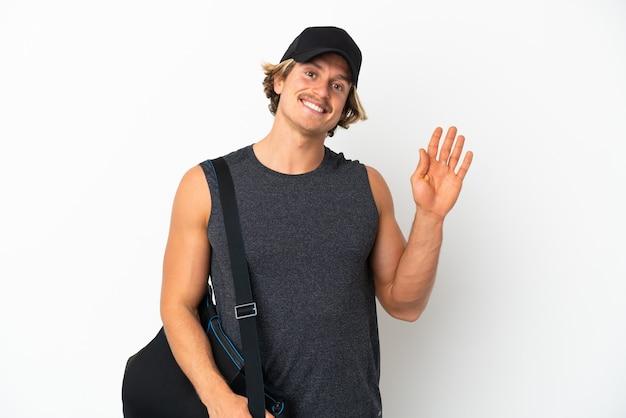 Молодой спортивный человек со спортивной сумкой на белом фоне салютует рукой с счастливым выражением лица