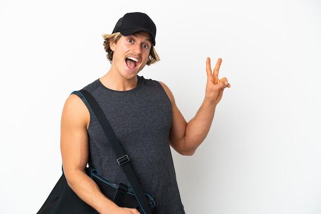 Молодой спортивный человек со спортивной сумкой на белом фоне улыбается и показывает знак победы