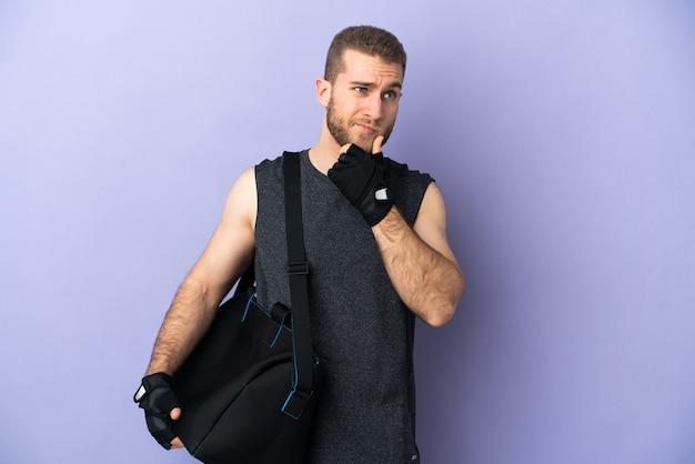 疑いと思考を持って白で隔離のスポーツバッグを持つ若いスポーツ男