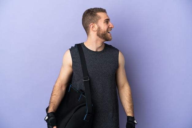 측면 위치에서 웃고 흰색에 고립 된 스포츠 가방 젊은 스포츠 남자