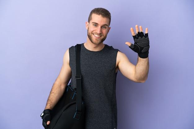 Молодой спортивный человек со спортивной сумкой, изолированной на белом, салютует рукой со счастливым выражением лица