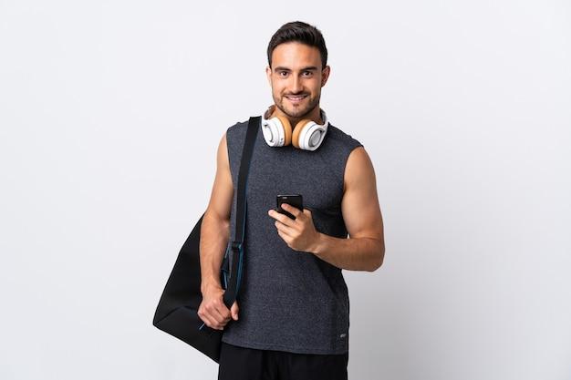 모바일로 메시지를 보내는 흰색 절연 스포츠 가방 젊은 스포츠 남자