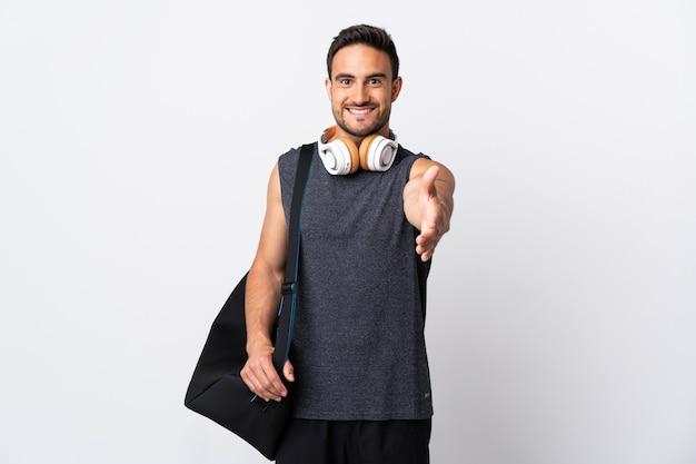 Молодой спортивный человек со спортивной сумкой, изолированной на белом, пожимая руку для заключения хорошей сделки