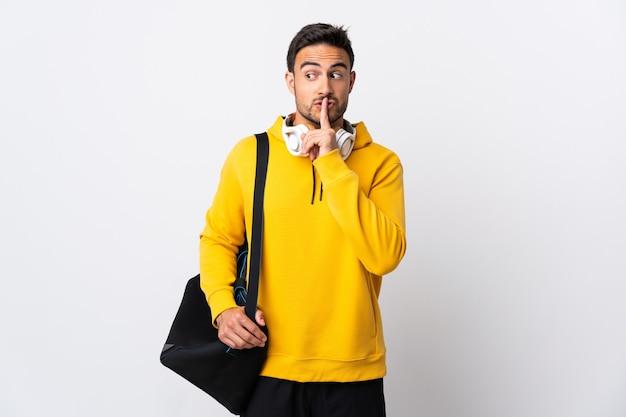 Молодой спортивный человек со спортивной сумкой, изолированной на белом, показывает знак жеста молчания, кладя палец в рот
