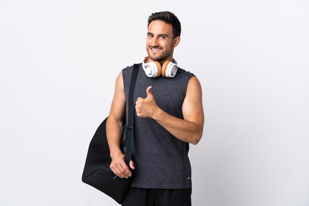 Молодой спортивный человек со спортивной сумкой, изолированной на белой стене, показывая жест пальца вверх