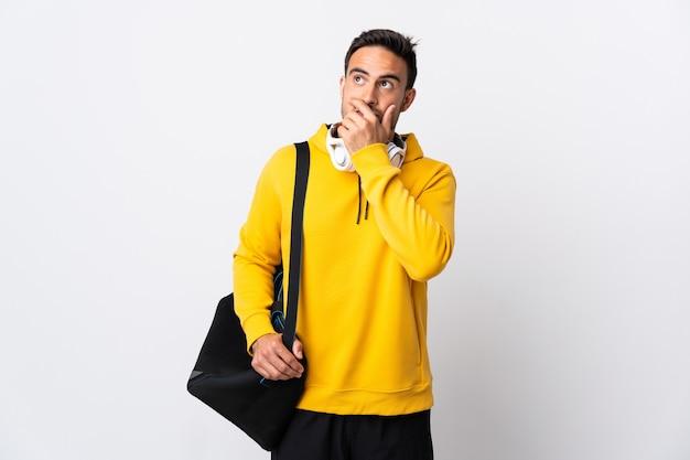흰색 벽에 의심이 있고 혼란스러운 얼굴 표정에 고립 된 스포츠 가방을 가진 젊은 스포츠 남자