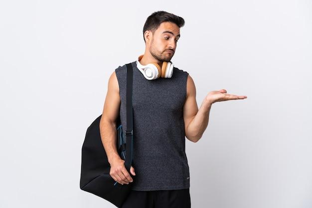Молодой спортивный человек со спортивной сумкой, изолированной на белой стене, держащей copyspace с сомнениями