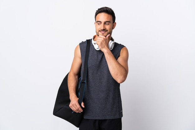 Молодой спортивный человек со спортивной сумкой, изолированной на белой стене, смотрит в сторону и улыбается