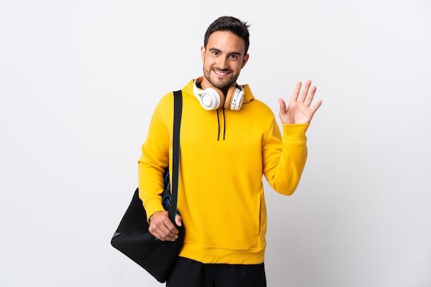Молодой спортивный человек со спортивной сумкой, изолированной на белой стене, салютует рукой со счастливым выражением лица