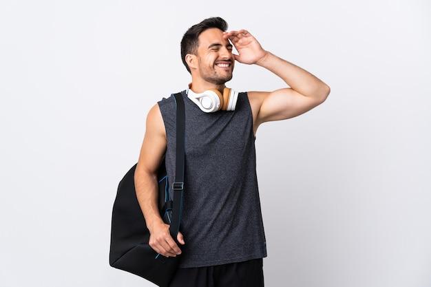 Молодой спортивный человек со спортивной сумкой, изолированной на белой стене, много улыбаясь