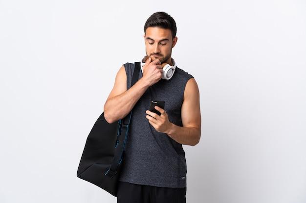 Молодой спортивный человек со спортивной сумкой, изолированной на белой стене, думает и отправляет сообщение