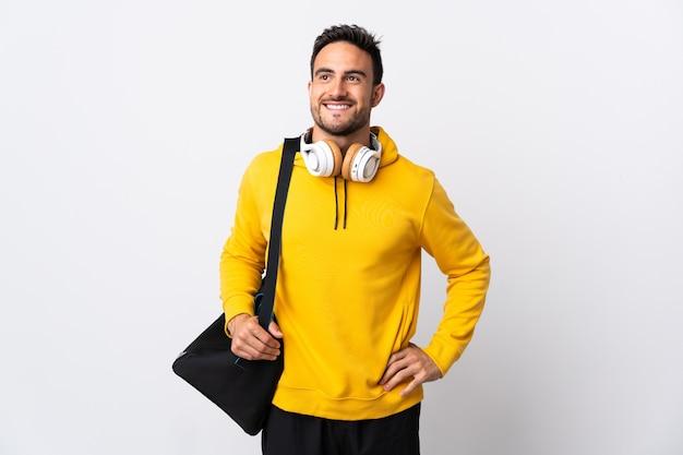 Молодой спортивный человек со спортивной сумкой изолировал, позирует с руками на бедрах и улыбается