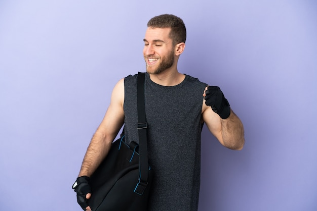 Young sport man with sport bag isolated on white celebrating a victory
