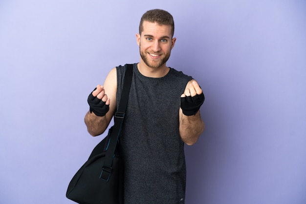 Young sport man with sport bag isolated on white making money gesture