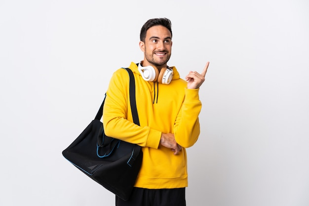 Young sport man with sport bag isolated on white wall pointing up a great idea