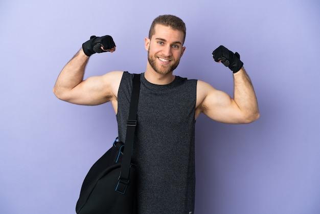 孤立したスポーツバッグを持つ若いスポーツ男