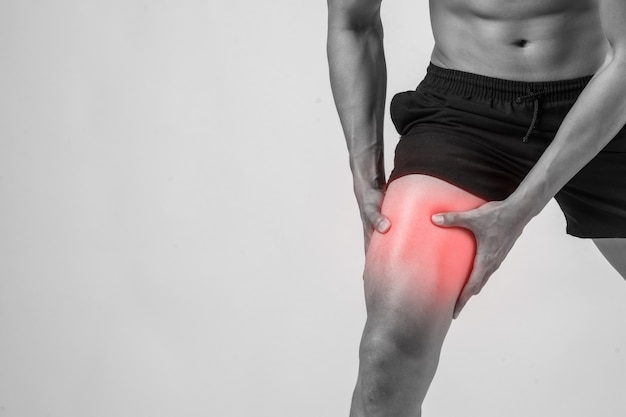 靭帯の傷害を苦しんだ後、痛みを伴う彼の手で膝を持つ強い運動脚を持つ若いスポーツマン。