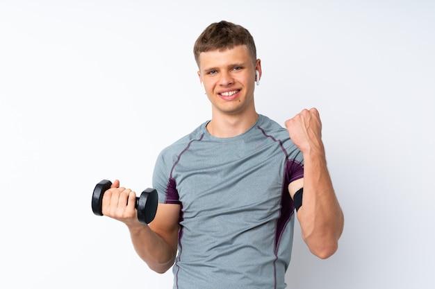Молодой спортивный человек с тяжелой атлетикой на белом фоне, празднует победу