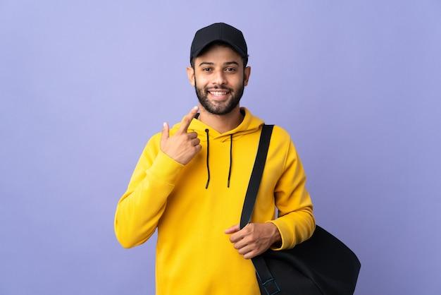 제스처를 엄지 손가락을주는 보라색 벽에 고립 된 스포츠 가방 젊은 스포츠 모로코 남자