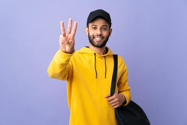 幸せな紫色の壁に分離されたスポーツバッグと指で3を数える若いスポーツモロッコ人