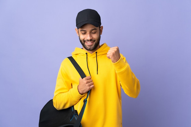 Young sport moroccan man with sport bag isolated on purple celebrating a victory