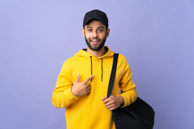 Young sport moroccan man with sport bag isolated on purple with surprise facial expression