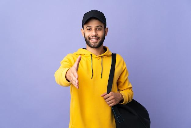 Молодой спортивный марокканский мужчина с изолированной спортивной сумкой