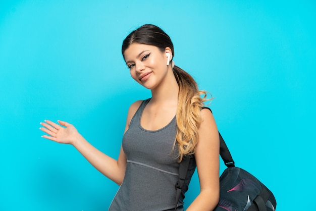 Young sport russian girl with sport bag isolated on blue background extending hands to the side for inviting to come