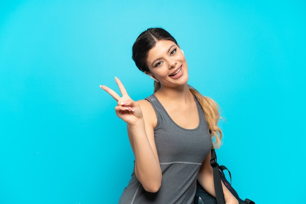 Young sport russian girl with sport bag isolated on blue background smiling and showing victory sign