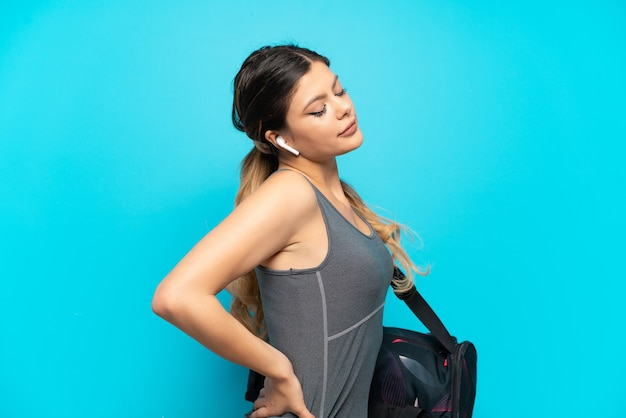 Young sport russian girl with sport bag isolated on blue background suffering from backache for having made an effort