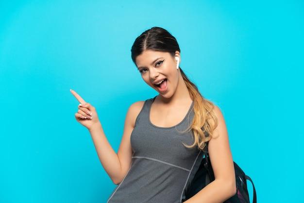 측면에 손가락을 가리키고 제품을 제시하는 파란색 배경에 고립 된 스포츠 가방 젊은 스포츠 러시아 소녀