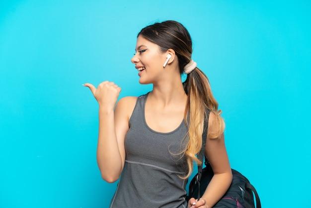 파란색 배경에 격리된 스포츠 가방을 들고 제품을 제시하기 위해 측면을 가리키는 젊은 스포츠 러시아 소녀