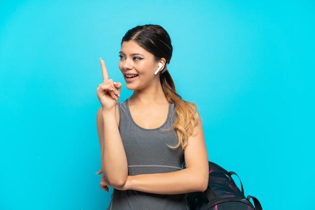 좋은 아이디어를 가리키는 파란색 배경에 고립 된 스포츠 가방 젊은 스포츠 러시아 소녀