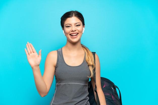 Молодая спортивная русская девушка со спортивной сумкой на синем фоне салютует рукой с счастливым выражением лица