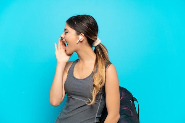 Молодая спортивная русская девушка со спортивной сумкой на синем фоне кричит с широко открытым ртом