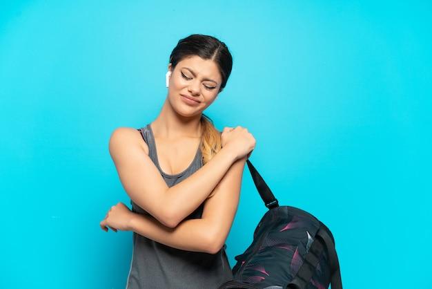 努力したために肩の痛みに苦しんでいる青い背景で隔離のスポーツバッグを持つ若いスポーツロシアの女の子
