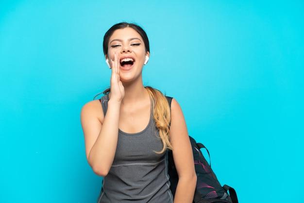 Молодая спортивная русская девушка со спортивной сумкой изолирована на синей стене и кричит с широко открытым ртом