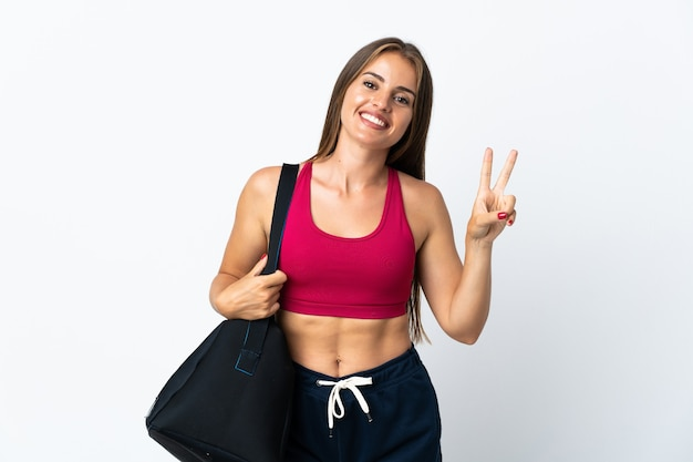 Молодая спортивная уругвайская женщина со спортивной сумкой на белом фоне улыбается и показывает знак победы